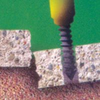 An illustration of a drill boring a hole into a slab of broken concrete.